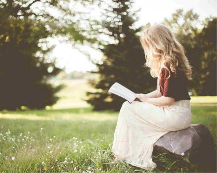 Vrouw zit op een steen in een groen gebied te lezen
